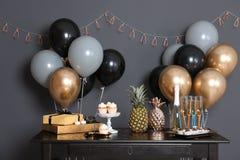 Festins et articles de partie sur la table dans la chambre photos stock