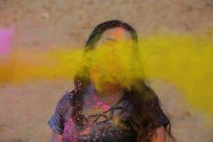 Festival appréciant modèle de Holi de brune fraîche au désert Femme posant avec éclater la peinture jaune photographie stock