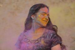 Festival appréciant modèle de Holi de brune heureuse au désert Femme posant avec éclater la peinture sèche photo stock