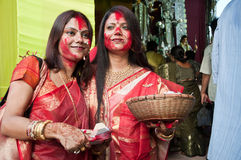 Festival of colors. CALCUTTA - OCTOBER 6: Beautiful Hindu women smear and play with vermilion during Sindur Khela traditional ceremony on the final day of Durga Stock Photography