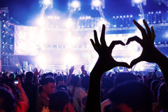 Festival crowd raising hands in music concert front of bright st. Age lights royalty free stock image
