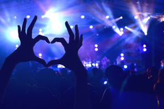 Festival crowd raising hands in music concert. Front of bright stage lights Royalty Free Stock Images