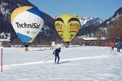 Festival de aerostación en las montañas austríacas en invierno blanco como la nieve entre esquiadores del campo a través fotos de archivo libres de regalías