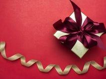 Festival de la tarjeta del día de San Valentín, caja de regalo del oro del Año Nuevo con la cinta roja Rojo Foto de archivo libre de regalías