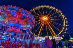 Festival de primavera en Munich en la hora azul con una noria aligerada y un carusel de cadena fotos de archivo