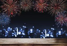 Festival fireworks at night in the city, wooden desk with Bokeh lights of building at night. For Holiday festival, New years Royalty Free Stock Photography