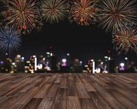 Festival fireworks at night in the city, wooden floor with Bokeh lights of building at night. For Holiday festival, New years and Royalty Free Stock Photos