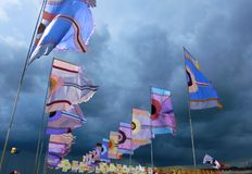 Festival flags waving against dramatic stormy sky. Brightly colored flags silhouetted by a dramatic stormy sky at Glastonbury music festival in the UK Royalty Free Stock Photography
