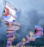 Festival flags waving against dramatic stormy sky. Brightly colored flags silhouetted by a dramatic stormy sky at Glastonbury music festival in the UK Royalty Free Stock Image