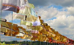 Festival flags waving in sunshine against dramatic sky. Brightly colored flags wave over tent rooftops at Glastonbury music festival in the UK Stock Image