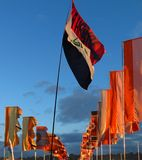 Festival flags waving in twilight against dramatic sky. Brightly colored flags wave against a twilight sky at Glastonbury music festival in the UK Stock Photography