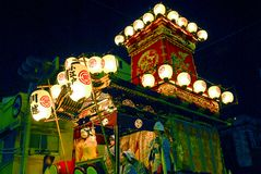 Festival float with musicians and daemon at night