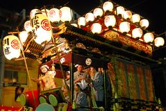 Festival float with musicians and daemon at night Stock Photo