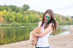 Festival holi, holidays, tourism and nature concept - young woman dressed in white shirt holding cat and covered with stock photo