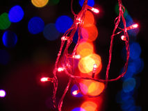 Festival Light Bulbs. A red light bulbs wire string on the backdrop of other colors blurred light for festive Christmas or Diwali decoration Royalty Free Stock Photos