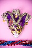 Festival Mardi Gras mask and multicolored beads on bright background. Studio Photo royalty free stock photo