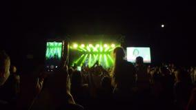 Festival musical, vidéo de disques de personne au téléphone portable sur la foule de fond dans les lumières lumineuses d'étape au banque de vidéos