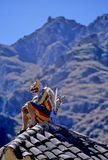 Festival- Peru. Danzaq (Andean demon) dancer resting atop house at the Fiesta Pentecostes in the Incan village of Ollantaytambo (Sacred Valley), Peru Royalty Free Stock Image