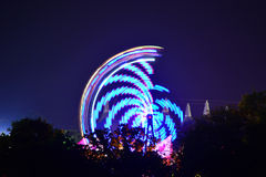 Festival Rides and Tree Silhouettes. The Big Top  and a spinning fairground ride create silhouettes with trees, at the Isle of Wight Music Festival in Newport Stock Photos