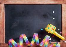 Festival Streamer, Confetti and Whistle on Board. Close up Colored Festival Paper Streamer, Confetti and Whistle on Black Board. Emphasizing Copy Space Stock Photo
