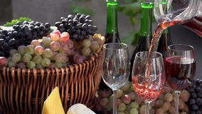 Festival of Young Wine. In pouring a glass of wine on the background of a basket with grapes, wine bottles and pieces of cheese. Slow Motion at a rate of 240 fps stock video