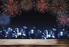 Festivalfyrverkerier på natten i staden, träskrivbord med Bokeh ljus av byggnad på natten För feriefestival nya år Royaltyfri Fotografi