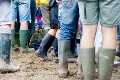 Festivalgoersuniversitetslärare deras wellies för den Glastonbury festivalen 2014 Arkivfoton
