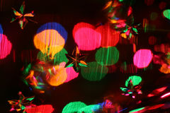 Festive abstract. Looking through a star etched crystal wine glass with multi-coloured mini lights behind Royalty Free Stock Image