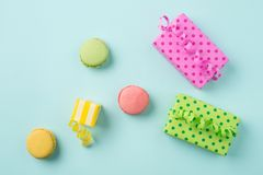 Festive abstract flat lay with colorful Gifts & macarons on ligh. Festive abstract composition with bright gift boxes, confetti & colorful macarons on light blue Stock Photography
