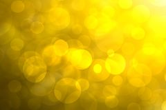 A festive abstract golden yellow gradient background texture with glitter defocused sparkle bokeh circles. Card concept for Happy royalty free stock image