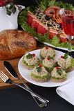 Festive appetizer: sandwich with pate against the backdrop of stuffed fish dishes Stock Photo
