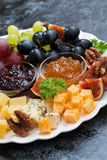 Festive appetizers - cheeses, fruits and jams, vertical closeup Royalty Free Stock Photo