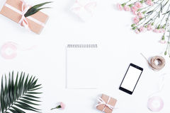 Festive arrangement: boxes with gifts, ribbons, notebook, mobile. Phone and flowers lie on a white table, top view Stock Photo