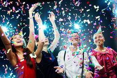 Festive atmosphere. Four friends making having fun among confetti royalty free stock images