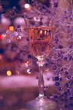 Festive atmosphere in the evening with a glass of champagne and a rainbow colored bokeh Royalty Free Stock Photos