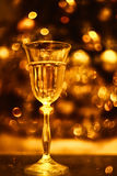 Festive atmosphere in the evening with a glass of champagne and a rainbow  golden lights Stock Photos