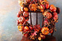 Festive autumn wreath with pumpkin and fall leaves. On an antique chair stock photo