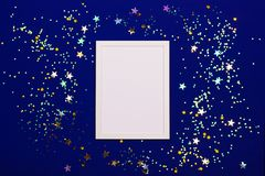 Festive background with blank white photo frame on dark blue with confetti. stock images