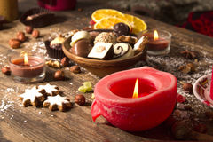 Festive background with candle, chocolate, nuts. And cookies Stock Image