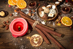 Festive background with candle, chocolate, nuts, cookies and. On a rustic wooden table Royalty Free Stock Photography