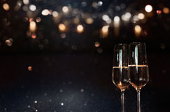 Festive background with champagne. Festive dark background with golden bokeh and champagne for christmas and new year Royalty Free Stock Photo