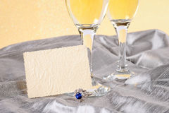 Festive background with champagne. Glasses an ring Royalty Free Stock Images