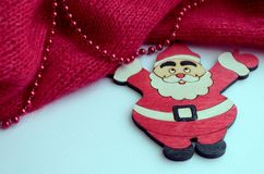 a picture with a red knitted canvas on which the beads lie. Nearby is a figure of Santa Claus stock photo