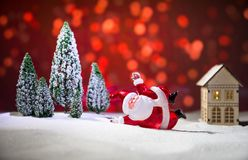 Festive background. Christmas decorations. Santa Claus (or Snowman) standing on snow with beautiful decorated background with. Holiday elements. Selective focus stock photo