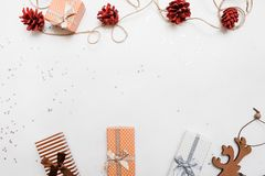 Festive background of Christmas holiday. Gift boxes on white background with silver star tinsels and strobila decoration above, top view with copy space Royalty Free Stock Images
