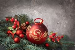 Festive background with Christmas tree twigs decorated with red. Baubles, ribon and frosted berries. Space for your text Royalty Free Stock Photo