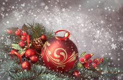 Festive background with Christmas tree twigs decorated with red. Baubles, ribon and frosted berries. Filtered image Stock Photo