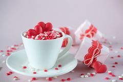 Festive background.  Coffee cup, full of multicolor sweet sprinkles sugar candy hearts and packing Valentine`s  Day gifts. Love and Valentine`s day concept Stock Image