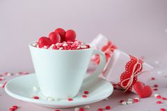 Festive background. Coffee cup, full of multicolor sweet sprinkles sugar candy hearts and packing Valentine`s Day gifts. Love and Valentine`s day concept royalty free stock photos