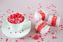 Festive background. Coffee cup, full of multicolor sweet sprinkles sugar candy hearts and packing Valentine`s Day gifts. Love and Valentine`s day concept royalty free stock images